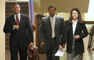 Attorney William Harrison walking with 2 other people
