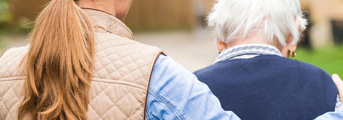 Woman with her arm around an elderly man