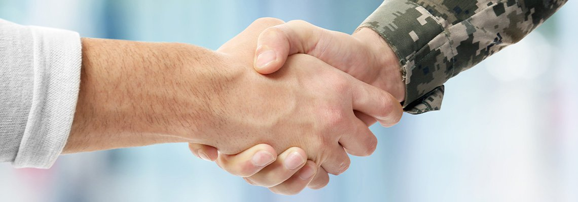 A civilian and military member shake hands