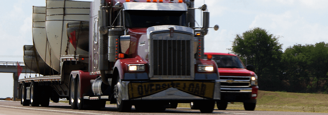 Red semi-truck driving on road next to truck