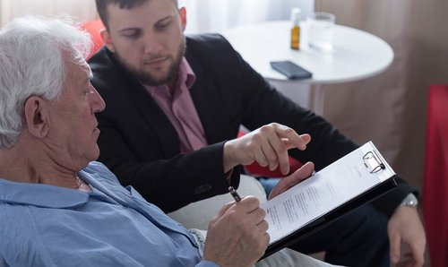 elderly man and younger man reviewing documents together