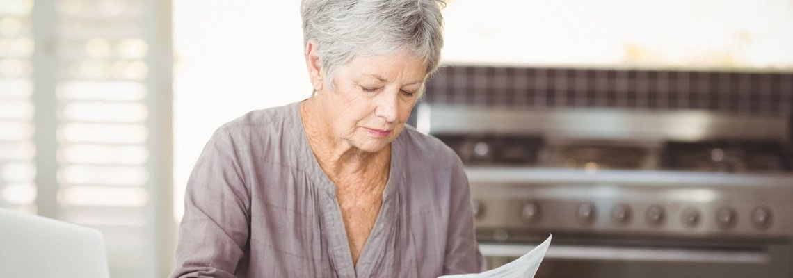 Older woman signing paper