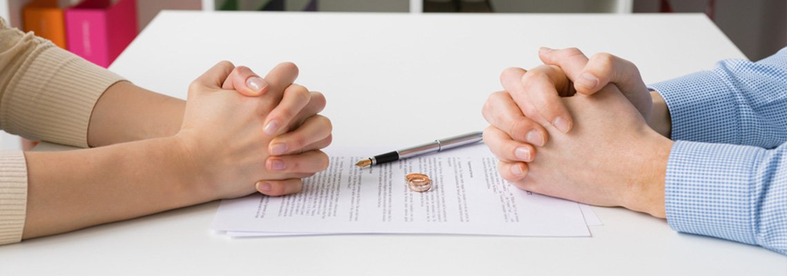 A couple prepares to sign their divorce papers