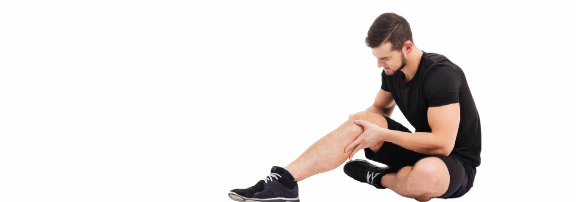 An injured man holding his knee