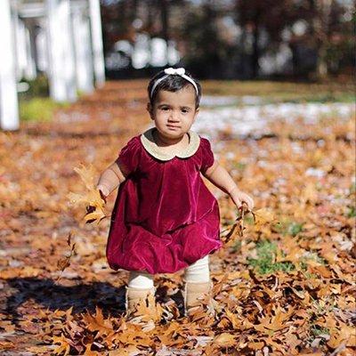 Little girl standing in autumn leaves