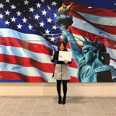 Young woman standing in front of a Statue of Liberty and American Flag