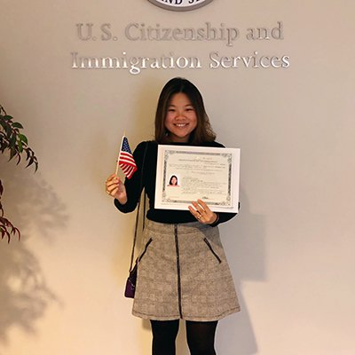 Woman holding a citizenship certificate at the United States Citizenship and Immigration Services