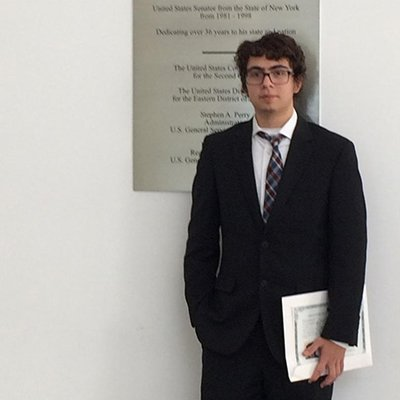 Young man standing with certificate in courthouse