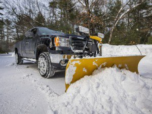 A black pickup truck plows snow into a big pile.