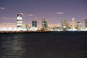 A city in New Jersey lights up as the sun is setting and the sky is purple.